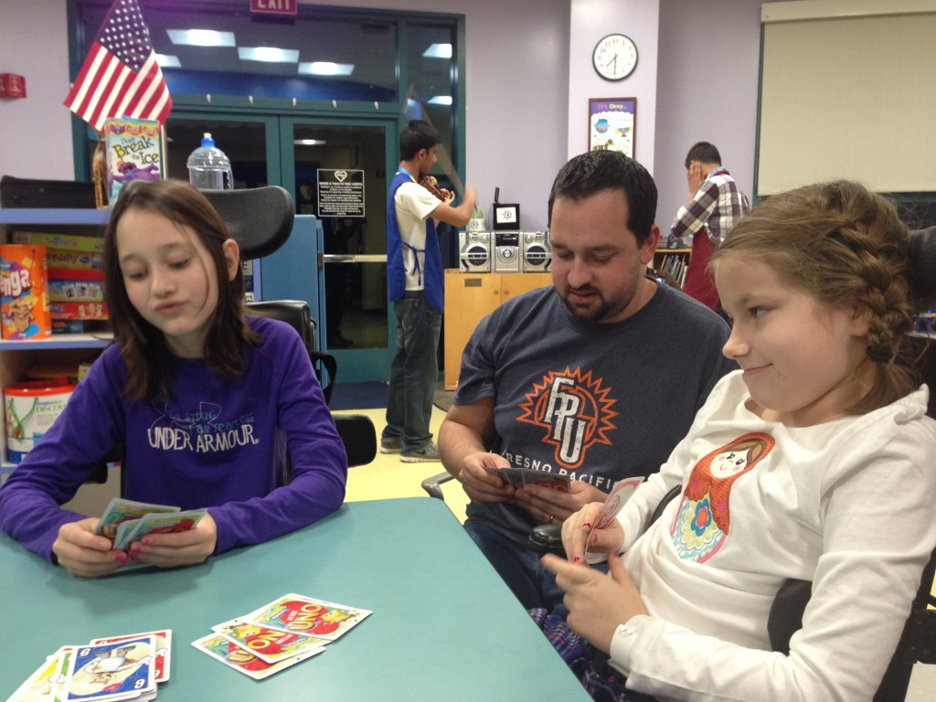 Playing card in Child Life with violinist in the background.